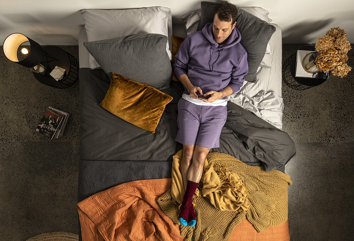 guy wearing purple resting on a bed playing with his phone