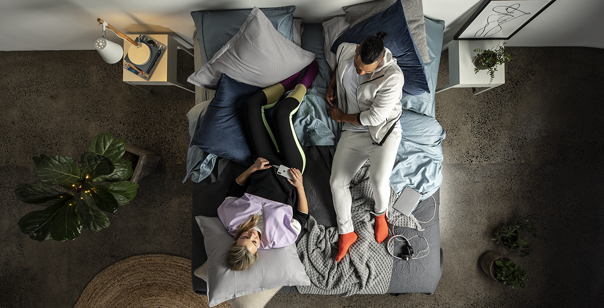 couple staring at one another on a bed