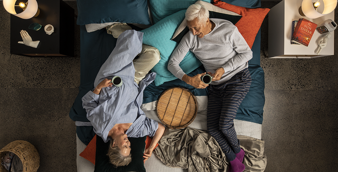 elderly couple lying on a huge bed smiling at each other
