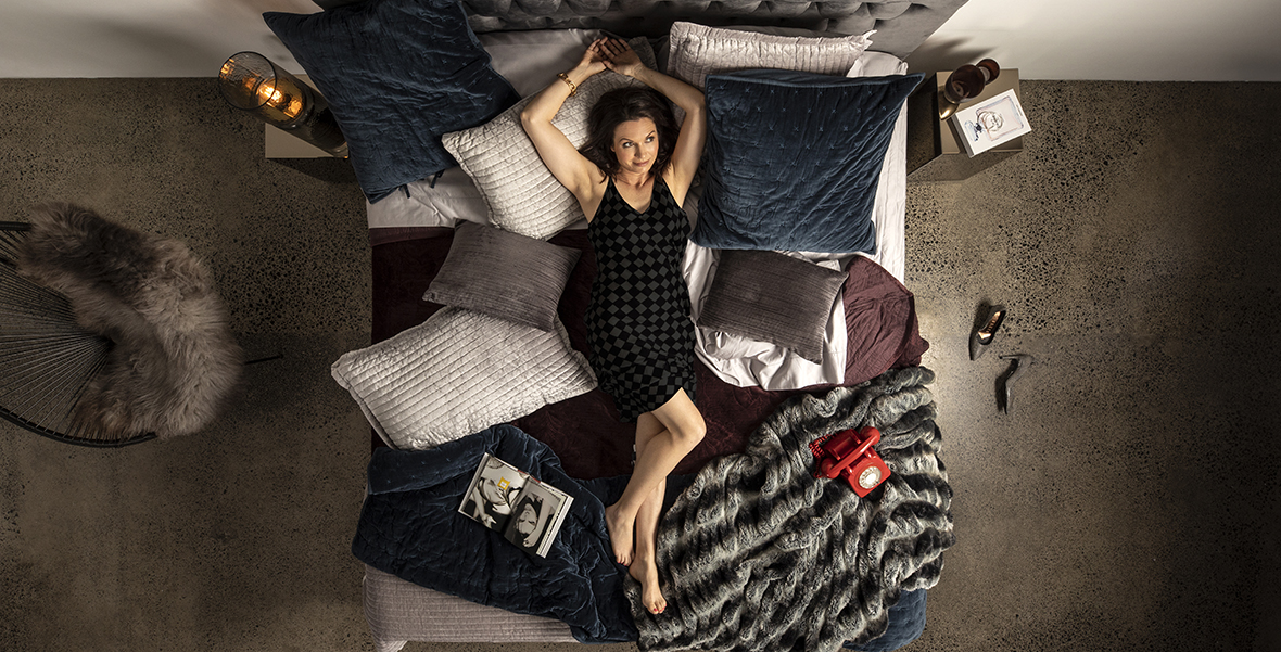 woman lying on bed filled with pillow